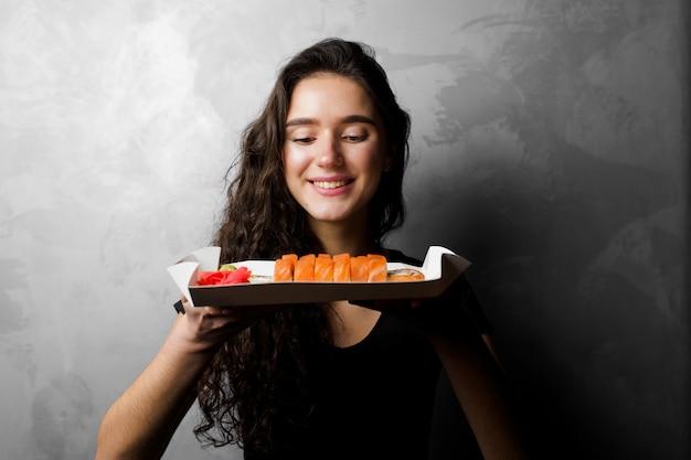 Menina segurando filadélfia rola em uma caixa de papel em fundo cinza. sushi, entrega de comida.
