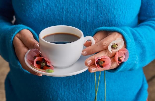 Menina segurando flores de papoula e uma xícara branca de café da manhã quente. fundo azul