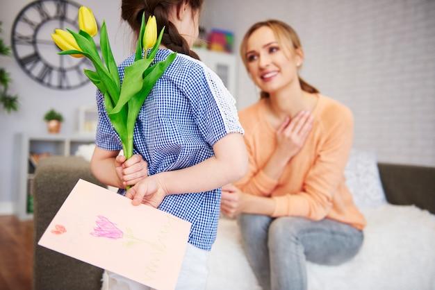 Menina segurando flores e um cartão comemorativo nas costas