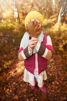 Menina segurando folhas de outono no rosto