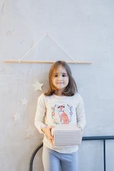 Menina segurando gif para ano novo ou natal, árvore de natal e interior decorado para ano novo, natal, antecipação de férias