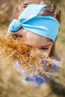 Menina segurando juncos secos nas mãos, clima ensolarado de primavera, sorrindo e a alegria da criança