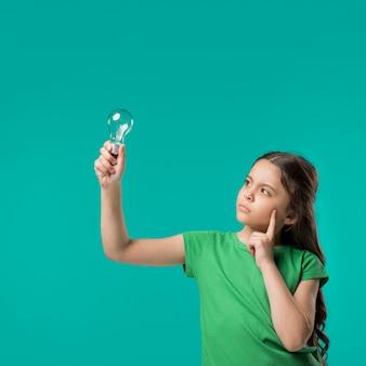 Menina, segurando, lâmpada, e, pensando
