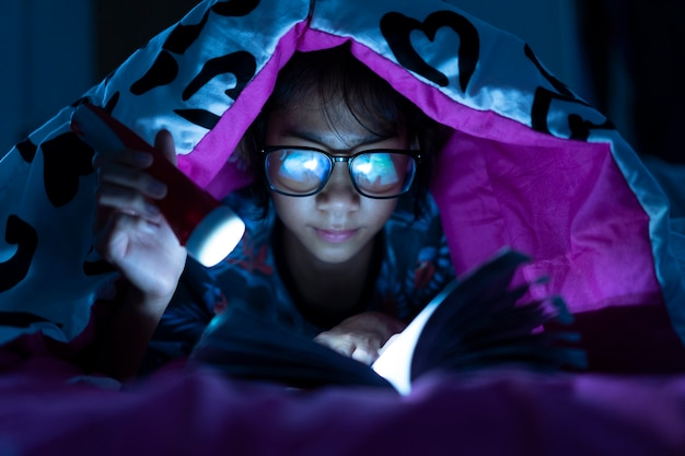 Menina, segurando, lanterna, enquanto, desgaste, óculos, leitura, livros, cobertor, em, cama, sala