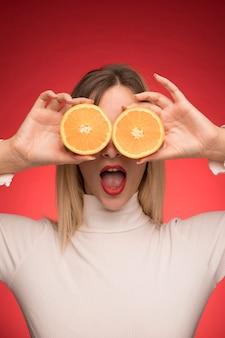 Menina, segurando, laranja, fatias, sobre, dela, olhos