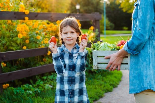 Menina segurando legumes orgânicos frescos