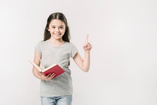 Menina, segurando, livro, com, levantado, dedo