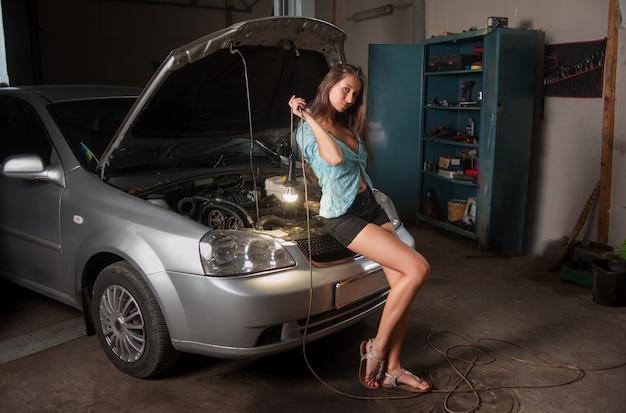 Menina, segurando, luz constante, bulbo leve, em, oficina carro, reparar