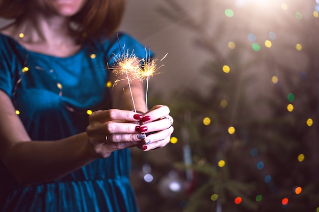 Menina segurando luzes de bengala - feliz natal e boas festas