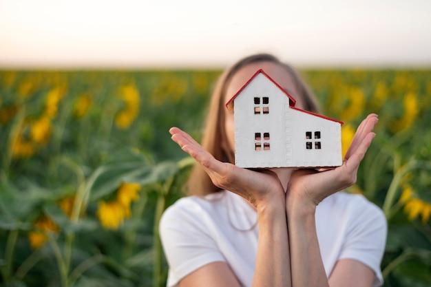 Menina segurando modelo de casa contra campo de girassóis