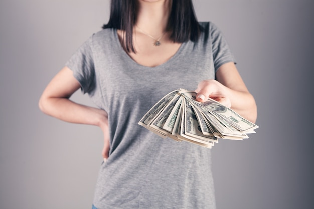 Menina segurando muito dinheiro nas mãos