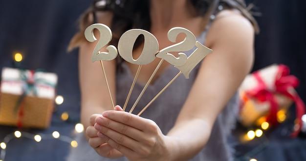 Menina segurando na mão o número do próximo ano em um fundo escuro e desfocado.