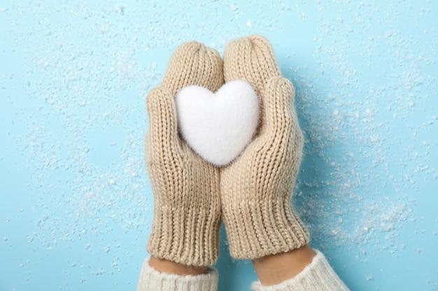 Menina segurando nas mãos coração branco na mesa azul com neve,