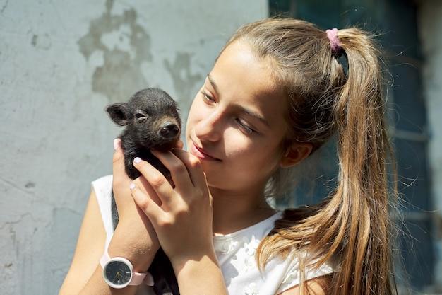 Menina segurando nas mãos de leitão preto bebê recém-nascido. fazenda, agricultura, país, animais de estimação, conceito de crianças