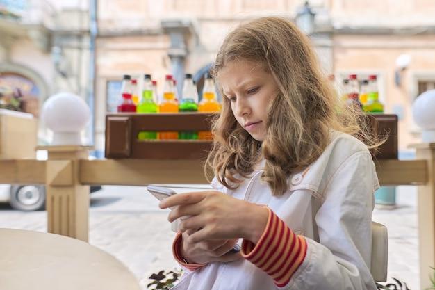 Menina segurando nas mãos e olhando para a tela do smartphone, sentada no café ao ar livre da cidade, copie o espaço