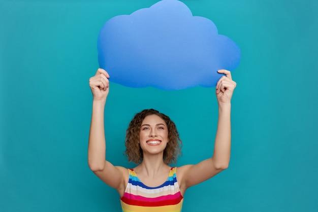 Menina segurando o balão em forma de nuvem acima da cabeça.