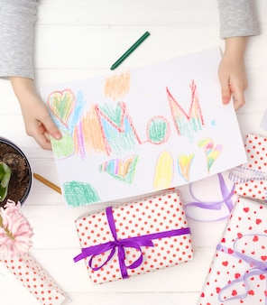 Menina, segurando o cartão do ofício para o dia da celebração mãe feliz