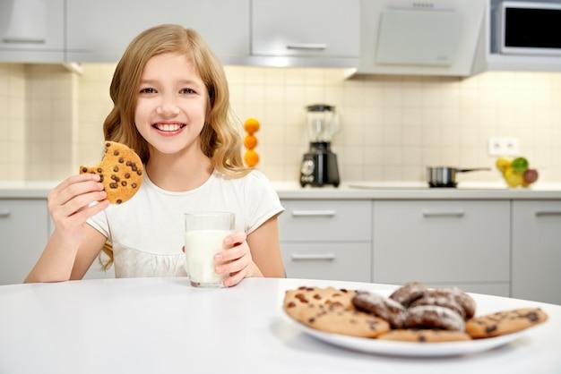 Menina segurando o copo de leite e biscoito, posando na cozinha.