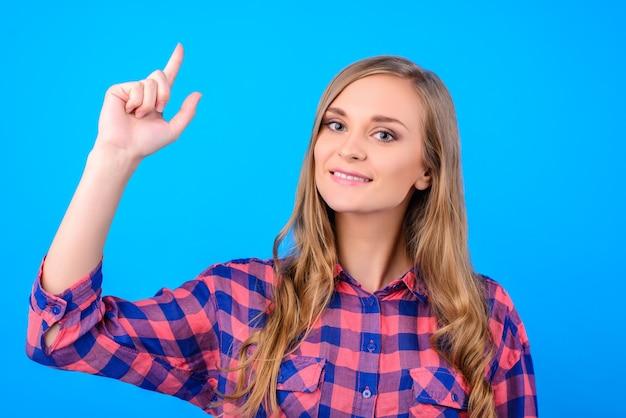 Menina segurando o dedo sobre fundo azul isolado