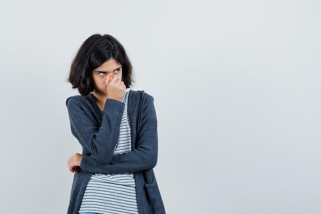 Menina segurando o nariz na camiseta, jaqueta e parecendo pensativa.