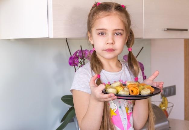 Menina segurando o prato com bolinhos de massa coloridos.