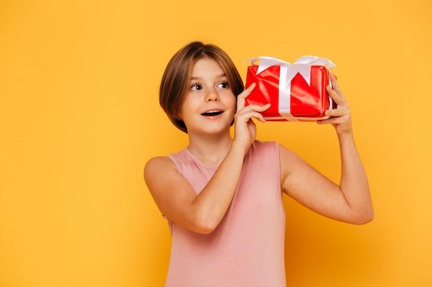 Menina segurando o presente e olhando de lado