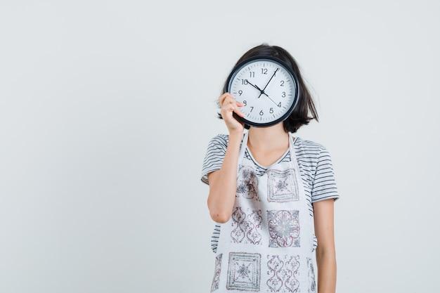 Menina segurando o relógio de parede sobre o rosto com camiseta, avental