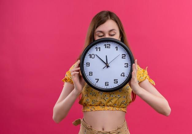 Menina segurando o relógio e se escondendo atrás dele, olhando para ele na parede rosa isolada com espaço de cópia