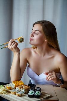 Menina segurando o rolo de sushi de pauzinhos. jovem mulher comendo um delicioso sushi japonês fresco.