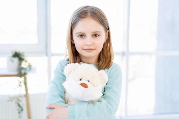 Menina segurando o ursinho de pelúcia