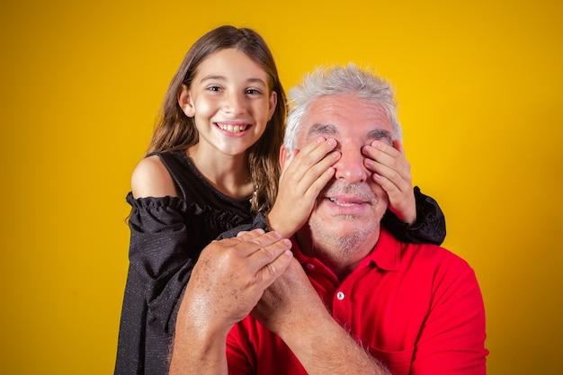 Menina segurando os olhos fechados do pai. fundo amarelo. dia dos pais. família brasileira.