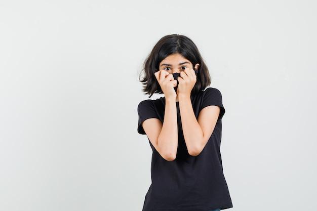 Menina segurando os punhos no rosto em t-shirt preta, máscara e olhando com medo, vista frontal.