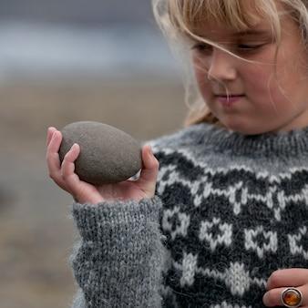 Menina, segurando, ovo, dado forma, pedra