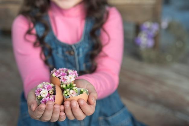 Menina, segurando, ovos quebrados, com, flores, em, mãos