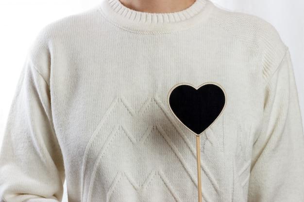 Menina segurando placa de coração preto