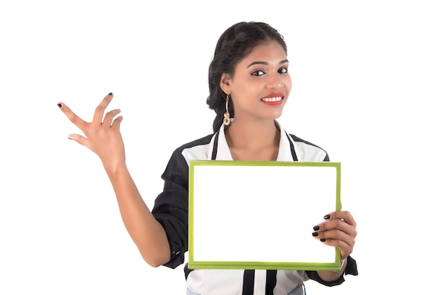 Menina segurando placa de sinalização branca em branco. retrato isolado