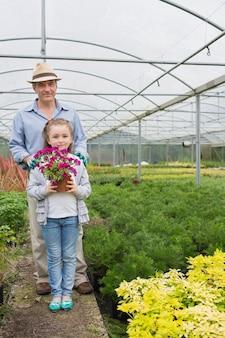 Menina segurando pote de flores de pé com seu avô