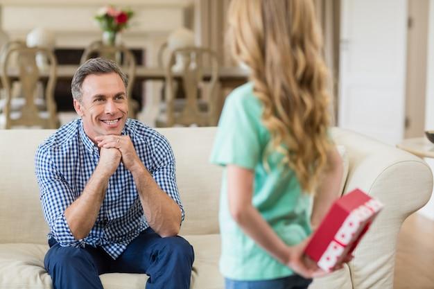 Menina segurando presente surpreso para o pai na sala de estar