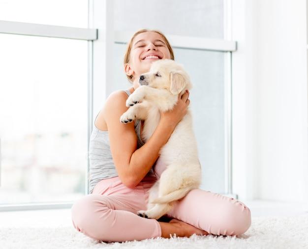 Menina, segurando, retriever, filhote cachorro