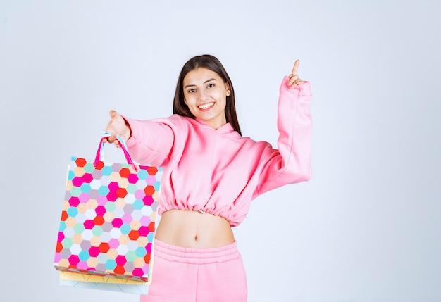 Menina segurando sacolas coloridas e apontando para algum lugar acima.
