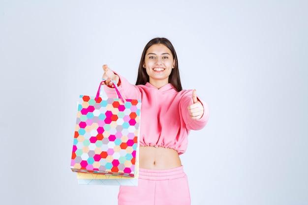 Menina segurando sacolas coloridas e parece animada.