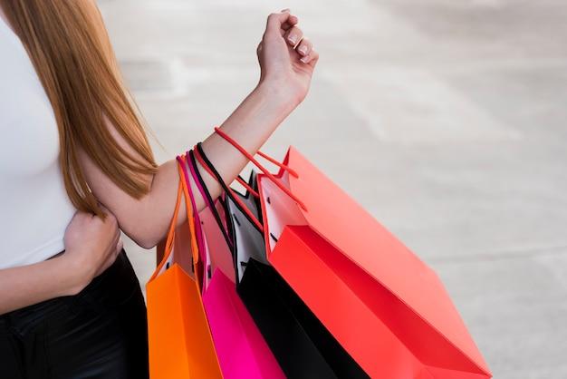 Menina segurando sacolas de compras no braço