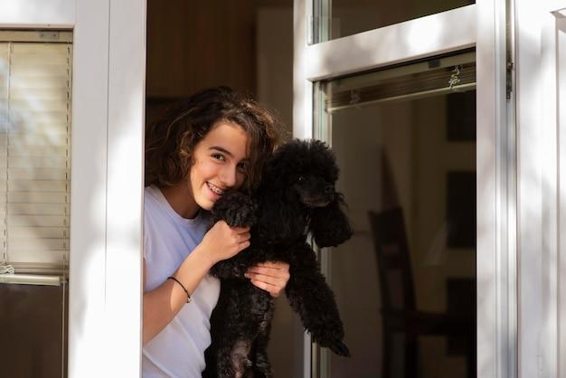 Menina segurando seu cachorro enquanto fica com uma janela aberta