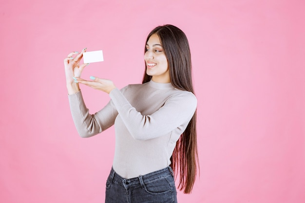 Menina segurando seu novo cartão de visita e se sentindo positiva