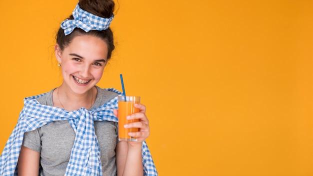 Menina segurando seu suco de laranja com espaço de cópia