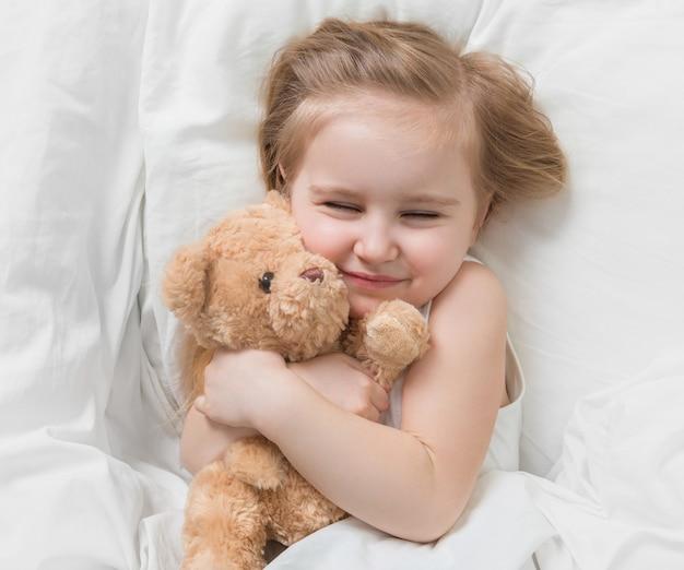 Menina segurando seu ursinho marrom, na cama