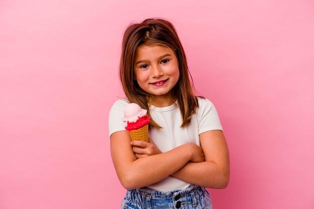 Menina segurando sorvete isolado na parede rosa, rindo e se divertindo