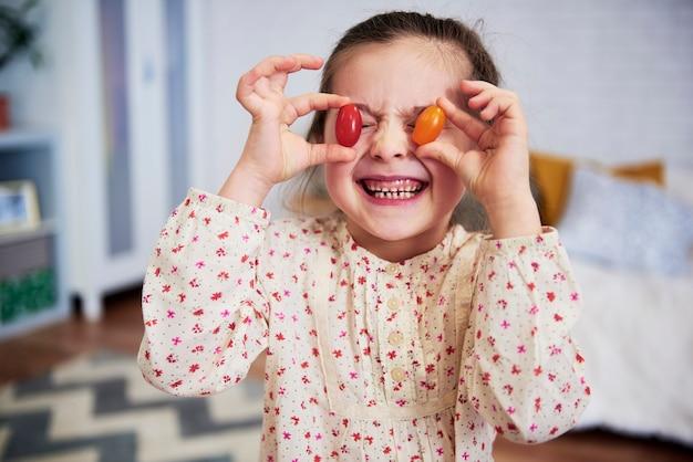 Menina segurando tomates na frente dos olhos