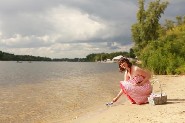 Menina segurando um barquinho de papel à beira do rio no verão
