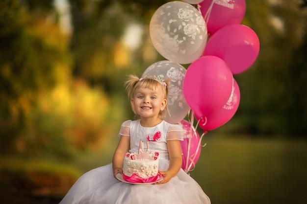 Menina segurando um bolo de aniversário com balões. copie o espaço